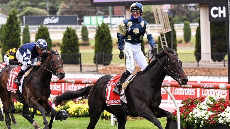 Glen Boss stands in the saddle to celebrate Sir Dragonet winning the 2020 Cox Plate